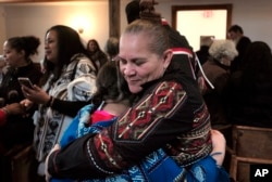 """Jessie """"Little Doe"""" Baird (R) hugs a member of the audience following celebration at the Old Indian Meeting House, in Mashpee, Mass., Nov. 18, 2017. Baird and other linguists are working reclaim the language of the Wampanoags, the tribe that helped the P"""