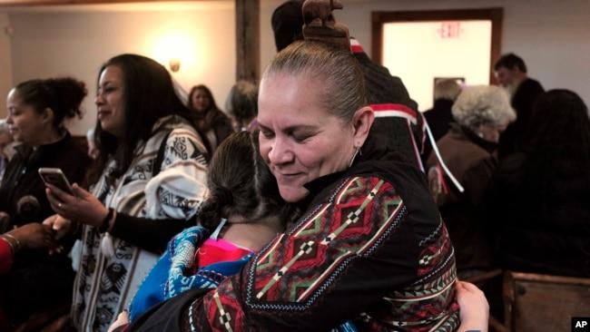 """Jessie """"Little Doe"""" Baird (R) abraza a un miembro de la audiencia luego de la celebración en Old Indian Meeting House, en Mashpee, Massachusetts, el 18 de noviembre de 2017."""