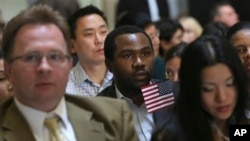 Zoltan Sznorfi, left, originally from Hungary, Benjamin Njoku, center, originally from Nigeria, and Keyan Chen, right, originally from China wait for the naturalization ceremony at historic Federal Hall to start, Friday, March 22, 2013 in New York.