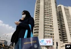 Seorang pejalan kaki mengenakan masker melintasi jalan di Teheran utara, Iran, Minggu, 1 Maret 2020. (Foto: dok).