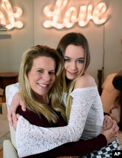 In this Feb. 28, 2018 photo, Matty Nev Luby, right, and her mother Kerrylynn Mahoney pose together for a photograph in Wethersfield, Conn. The high school gymnast's popularity on the lip-syncing app Musical.ly, which merged this summer into the Chinese vi