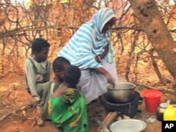 A woman prepares a meal for several children. There is no electricity or running water in homes, and food often is in short supply at the Kakuma Refugee Camp, Aug 2010