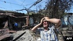 一名乌兹别克人站在自己被烧毁的房舍旁