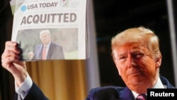 Eski Başkan Trump, geçen yıl ilk azil davasında beraat etmesinin ardından 6 Şubat 2020'de Washington'da katıldığı Ulusal Dua Kahvaltısı'nda USA Today gazetesinin baş sayfasında yer alan haberi gösteriyor.