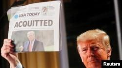 Rais wa zamani wa Marekani Donald Trump akionyesha gazeti la USA Today likiwa na habari za Baraza la Senetikumuondolea mashtaka kwa tuhuma za kutumiavibaya madaraka na kuingilia kati Bunge la Marekani, Washington, Marekani, February 6, 2020. REUTERS/Leah Millis