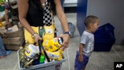 FILE - A shopper in a Caracas supermarket holds her basket of products that have been in short supply, Feb. 3, 2015.