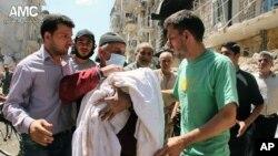 Seorang lelaki Suriah membawa jasad korban serangan udara dari pemerintah Suriah di Aleppo, 28/5/2014.
