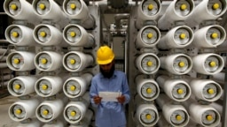 FILE - A worker stands at a desalination plant, 35 km south of Riyadh, May 4, 2011.