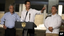Venezuela's opposition leader Juan Guaido speaks flanked by Chile's President Sebastian Pinera, left, and Colombia's President Ivan Duque in front of a warehouse housing U.S. humanitarian aid destined for Venezuela, in Cucuta, Colombia, Feb. 22, 2019.
