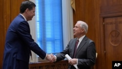 Attorney General Jeff Sessions shakes hands with FBI Director James Comey, left, at the start of a meeting with the heads of federal law enforcement components at the Department of Justice in Washington, Feb. 9, 2017.
