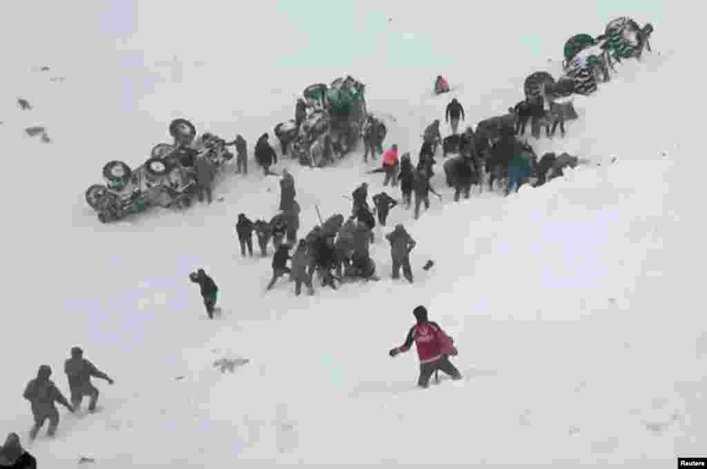 Turkish soldiers and locals rescue people trapped under avalanche in Bahcesaray in Van province, Turkey, in this still image taken from video. (Credit: Ihlas News Agency)