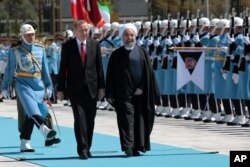 FILE - Turkey's President Recep Tayyip Erdogan, left, and Iran's President Hassan Rouhani inspect a military honour guard during a welcome ceremony in Ankara, Turkey, April 16, 2016.