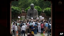 Media personnel surround opposition lawmakers protesting near a Mahatma Gandhi statue on Parliament premises in New Delhi, India, Aug. 6, 2015.