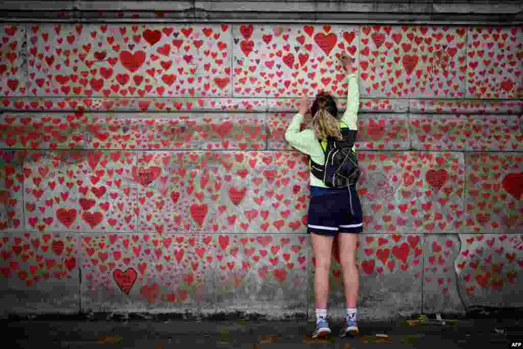A woman draws on the National Covid Memorial Wall on the embankment on the south side of the River Thames in London.