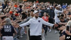 Ty Jerome and other members of the Virginia basketball team are welcomed by fans as they return home after their win of the championship in the Final Four NCAA college basketball tournament against Texas Tech, in Charlottesville, Va., Tuesday, April 9, 2019.