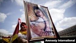 Seorang peziarah dari Meksiko membawa lukisan Paus Yohanes Paulus II saat berada di Alun-Alun Santo Petrus di Vatikan (26/4). (AP/Andrew Medichini)