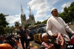 Umat Muslim Indonesia tiba di masjid Istiqlal yang terletak di seberang Katedral Jakarta pada 29 Maret 2013. (Foto: AFP)