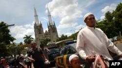 Seorang pria Muslim tiba di masjid Istiqlal yang terletak di seberang Katedral di Jakarta.