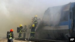 Israeli fire fighters spray water to extinguish the flames of a burning train coach near Kibbutz Shfaim, close to the Israeli city of Netanya about 15 kms (nine miles) north of Tel Aviv, after the passenger train caught fire on 28 Dec 2010