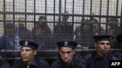 Policajci ispred kaveza u kojem su egipatski službenici nekoliko pro-demokratskih grupa tokom sudjenja u Kairu, Egipat, 26. februar, 2012.