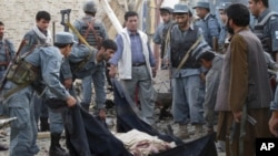 Afghan police officers wrap the body of a hotel guard in a black cloth after a suicide attack in Kunduz, north of Kabul, Afghanistan, August 2, 2011