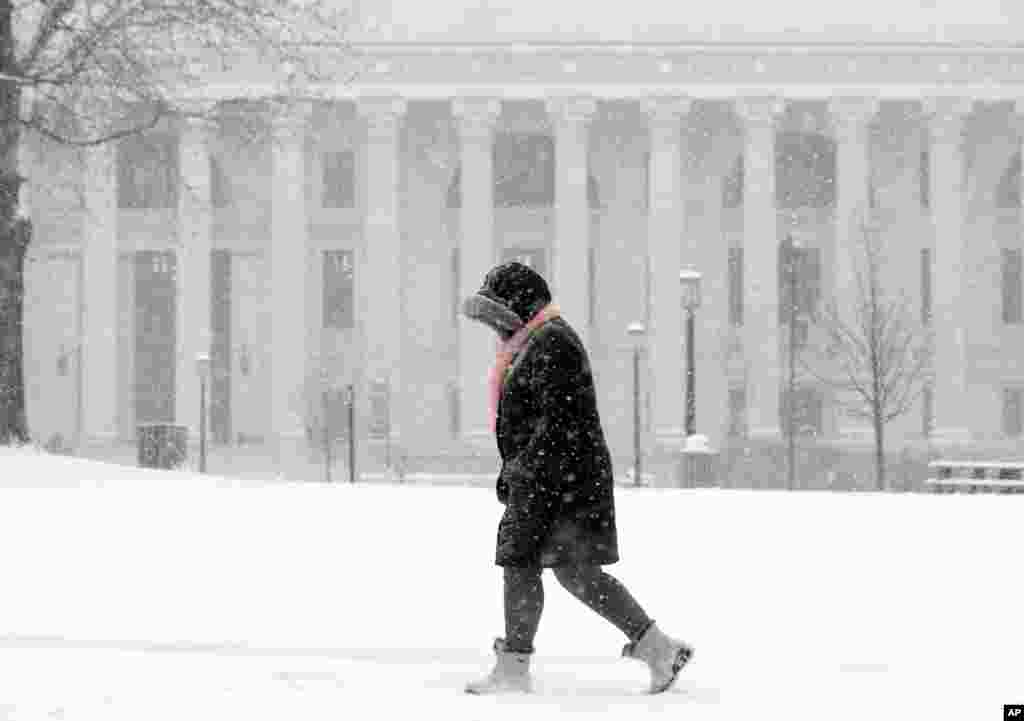 A pedestrian walks in the snow in Albany, New York. An early spring cold front is bringing snow and gusty winds to the Northeast after the region had one of its mildest winters on record.