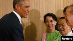 Myanmar opposition leader Aung San Suu Kyi (C) looks on as U.S. President Barack Obama shakes hands after a roundtable with members of parliament in Naypyitaw November 13, 2014.