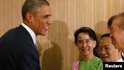 Myanmar opposition leader Aung San Suu Kyi (C) looks on as U.S. President Barack Obama shakes hands after a roundtable with members of parliament and civil society to discuss Myanmar's reform process, in Naypyitaw November 13, 2014. Obama is in Myanmar to