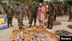 FILE - Military officials stand near ammunitions seized from suspected members of Hezbollah after a raid of a building in Nigeria's northern city of Kano, May 30, 2013.