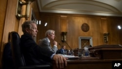 Sen. Rand Paul, R-Ky., left, and Sen. Rob Portman, R-Ohio, pose questions to witnesses as the Senate Committee on Foreign Relations holds a hearing on relations between the U.S. and Russia, on Capitol Hill in Washington, Aug. 21, 2018.