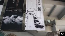 """台北市立美术馆大厅悬挂的巨幅海报上写着""""艾未未·缺席"""",人像的头也缺席了。"""