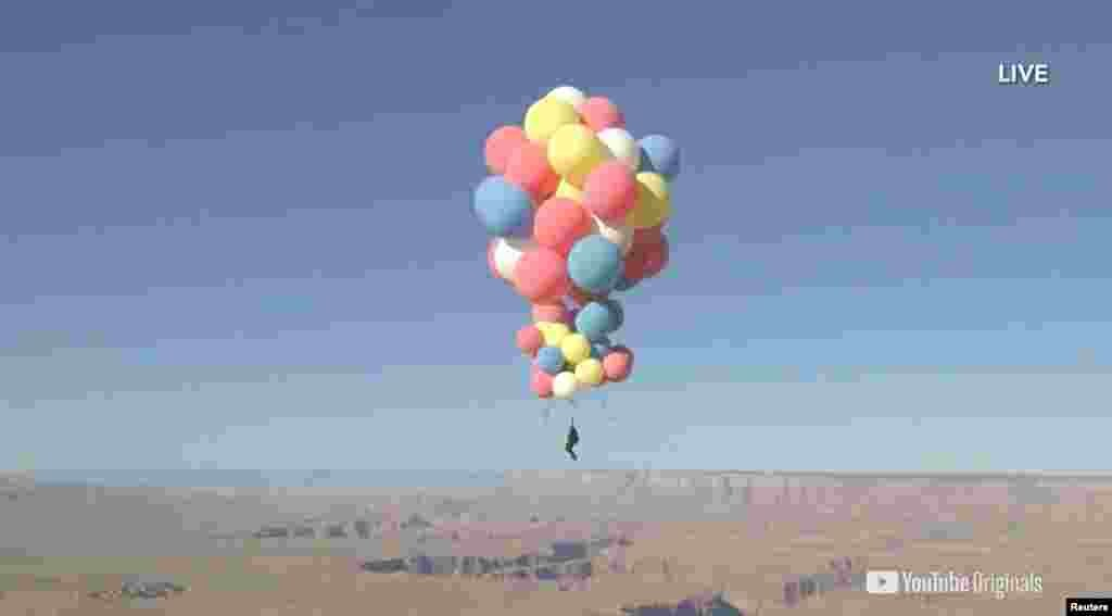 Extreme performer David Blaine hangs with a parachute under a cluster of balloons during a stunt to fly thousands of feet into the air in a still image from video taken over Page, Arizona, Sept. 2, 2020. (David Blaine/Handout)