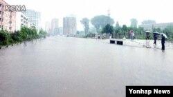 지난 2012년 8월 평양에 내린 폭우로 일부 도로가 침수되어 시민들이 통행에 불편을 겪고 있다. 물에 잠긴 평양 시내 모습이 조선중앙통신 홈페이지에 게재되었다. (자료사진)