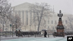 Snow and freezing rain fall on the Supreme Court and Capitol in Washington, prompting many agencies of the federal government to close for the wintry weather, Dec. 10, 2013.