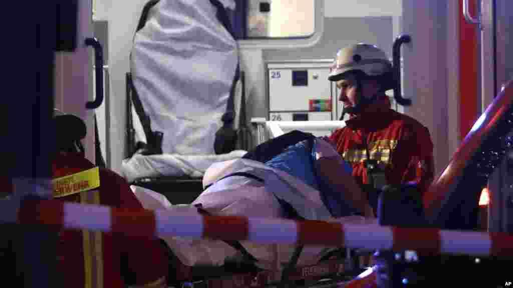 Des pompiers transportent un blessé dans une ambulance après qu'un camion a foncé dans un marché de Noël et tué plusieurs personnes à Berlin, Allemagne, 19 décembre 2016.
