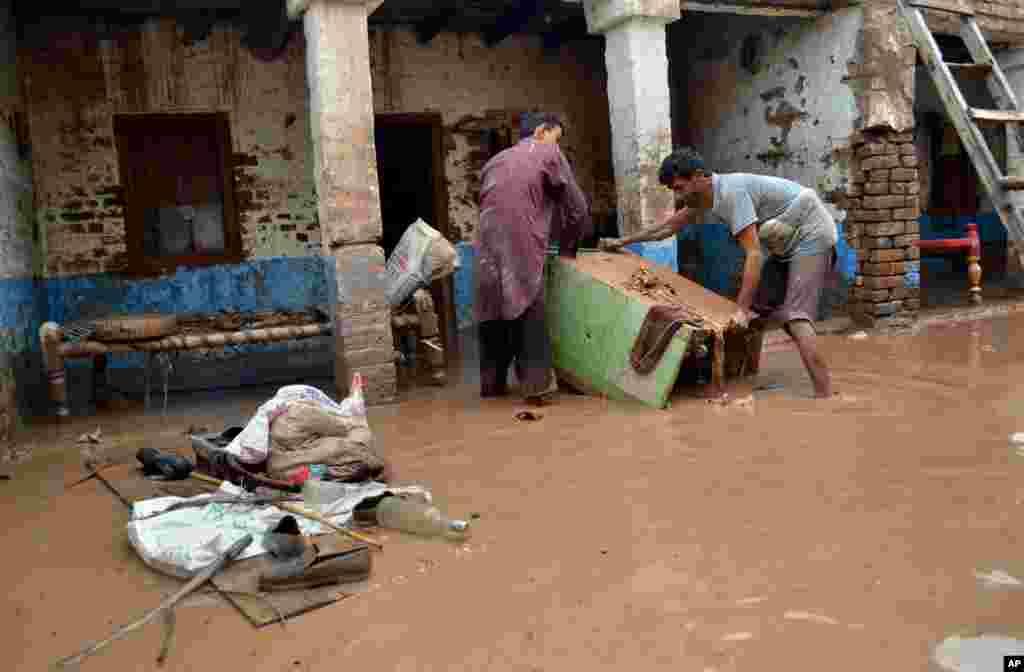 3일 파키스탄 페샤와르에서 장마로 주택가가 침수된 가운데, 주민들이 물건을 꺼내고 있다.