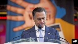 El candidato republicano Mitt Romney hace una pausa durante su discurso ante la Asociación Nacional para el Progreso de las Personas de Color, mientras es abucheado por rechazar el plan de salubridad de Obama, ante una audiencia de afroestadounidenses.