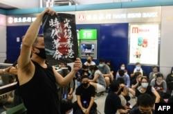 """2019年8月21日,香港示威者在元朗西铁站高举海报,抗议他们指责的""""警黑勾结""""导致元朗暴徒袭击示威者事件。"""
