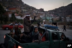 FILE - Taliban fighters sit on the back of a pickup truck as they stop on a hillside in Kabul, Afghanistan, Sept. 19, 2021.