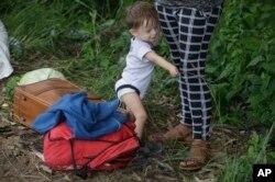 Un bebé se sostiene en la pierna de una mujer mientras viajan en una caravana de migrantes hondureños que se desplazan hacia Guatemala, en Ocotepeque, Honduras, el lunes 15 de octubre de 2018. La mujer y el pequeño forman parte de un grupo de migrantes hondureños que pretenden llegar caminando a Estados Unidos.