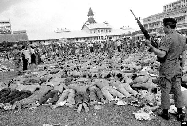FILE - In this Oct. 6, 1976 file photo, police stand guard over leftist Thai students on a soccer field at Thammasat University, in Bangkok, Thailand. For some Thais, the bloody events of October 6, 1976 are still a nightmare. On that day, heavily armed s