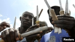 Ugandan traditional surgeons display circumcision knives before initiation ceremony, Mbale, Aug. 2008.