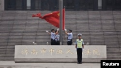 FILE - Policemen hoist a Chinese national flag at the entrance of a court in Jinan, where former disgraced politician Bo Xilai was held, September 22, 2013.