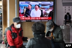 People watch a television news broadcast showing file footage of North Korean leader Kim Jong Un, at a railway station in Seoul on April 21, 2020.