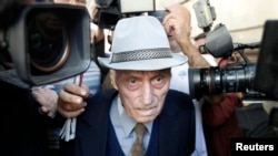 FILE - Alexandru Visinescu, the commander of the Ramnicu Sarat prison in eastern Romania between 1956 and 1963 while the country was under communist rule, leaves a court in Bucharest, Sept. 24, 2014.