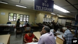 An Indian woman, foreground left, waits to send a telegram at Bharat Sanchar Nigam Limited (BSNL), a state-run telecom company in Bangalore, India, June 14, 2013.