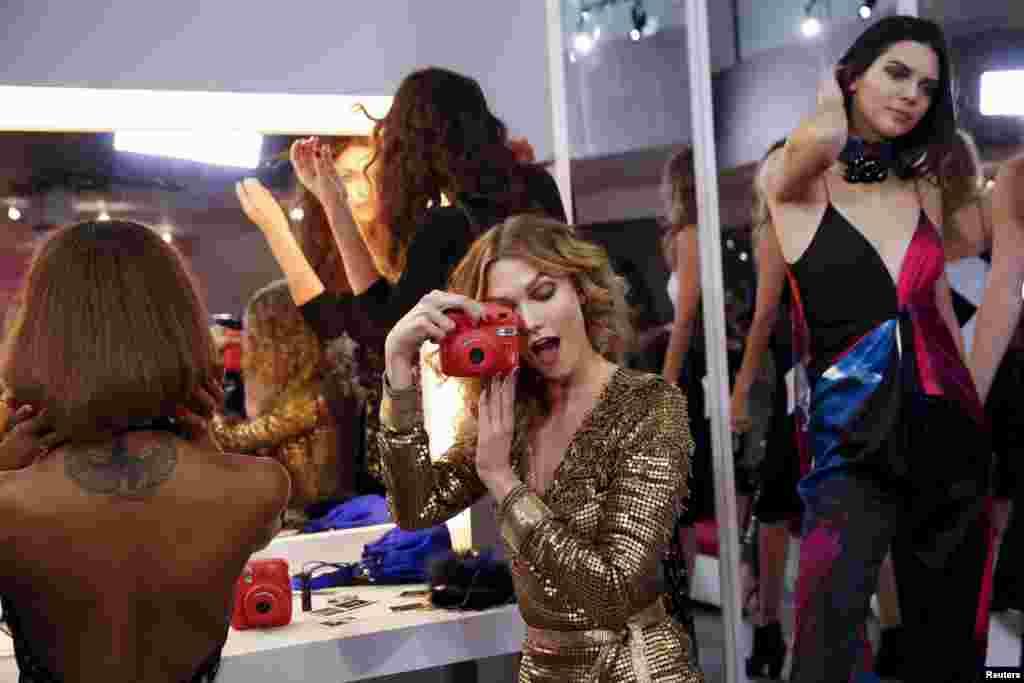 Modelo Karlie Kloss brinca com a sua câmara antes de desfile em Nova Iorque.