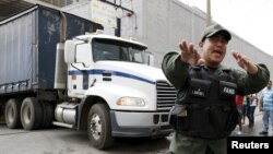 A Venezuelan National Guard walks in front of a truck as it leaves the facility used by Empresas Polar as a distribution center, while company employees shout inside, during the occupation of its installations by government representatives in Caracas, July 30, 2015.