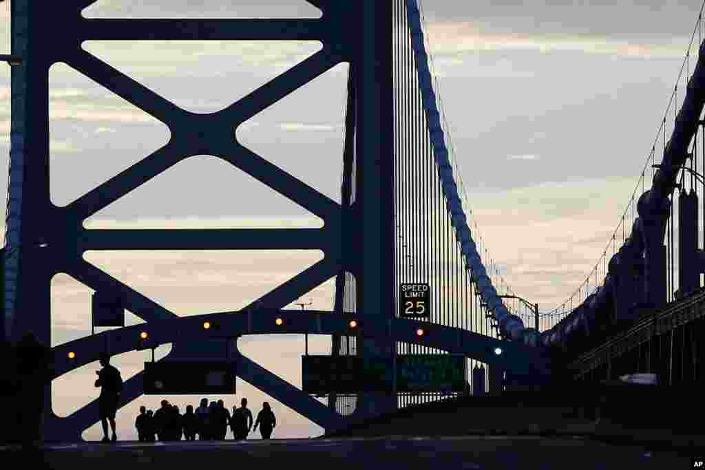 A family from Trenton, New Jersey, walks over the Benjamin Franklin Bridge ahead of a Sunday Mass to be delivered by Pope Francis in Philadelphia, Pensylvania, before flying back to Rome.