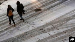 FILE - Pedestrians leave footprints in the snow as they cross a street in downtown Kansas City, Missouri, Dec. 17, 2016. A new winter storm featuring freezing rain is expected to hit the nation's mid-section Friday, Dec. 13, 2017.